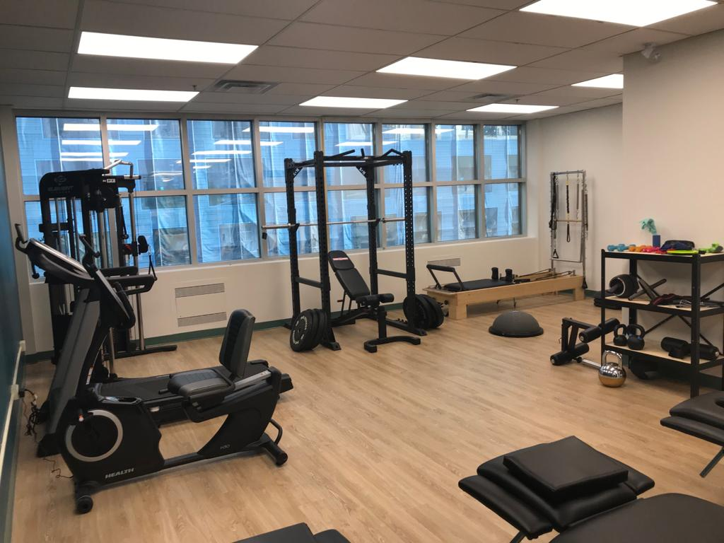Large gym with squat rack, and pilates reformer